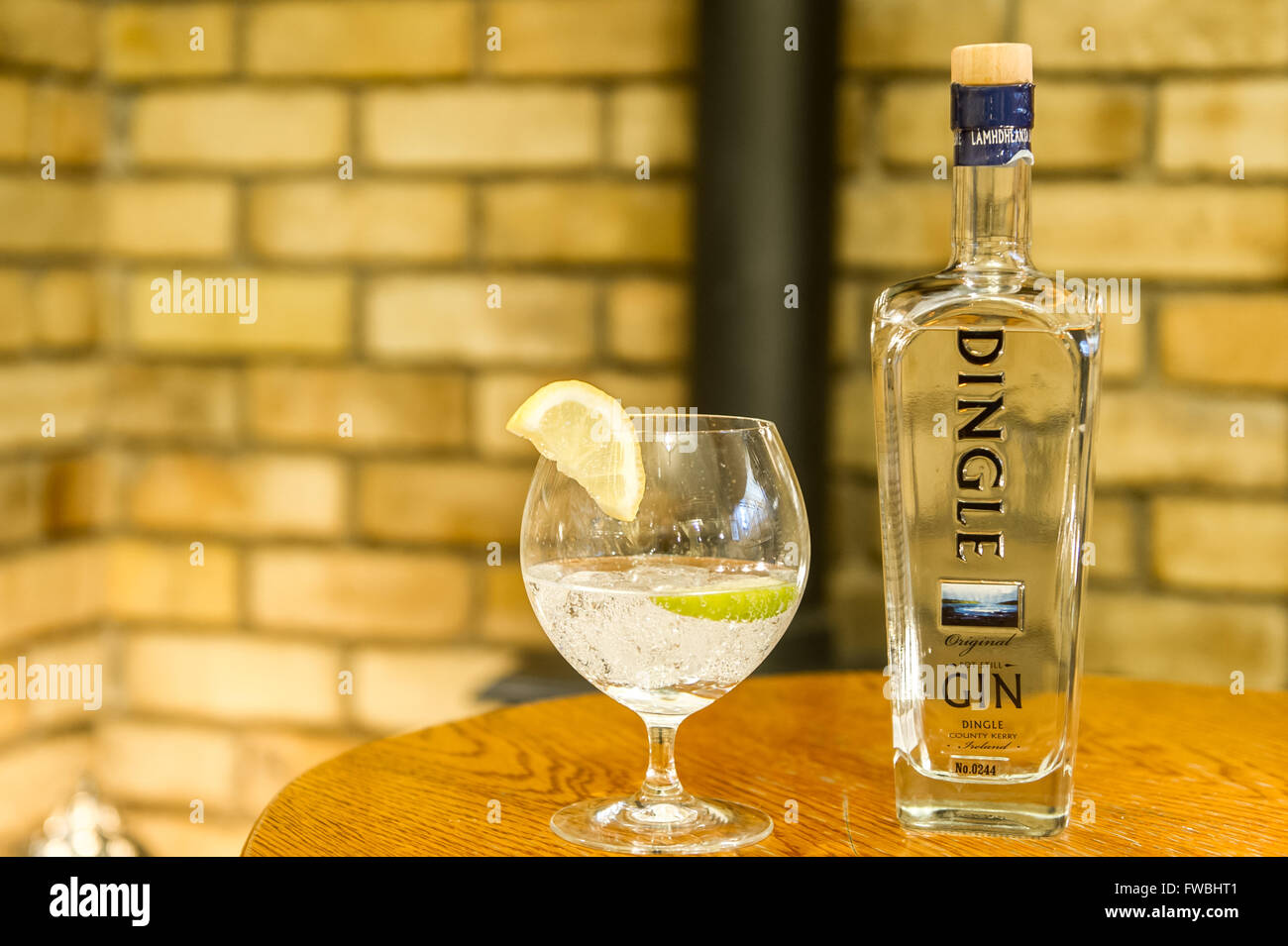 Bottle of Dingle Gin and a glass of gin with ice and lemon. - Stock Image