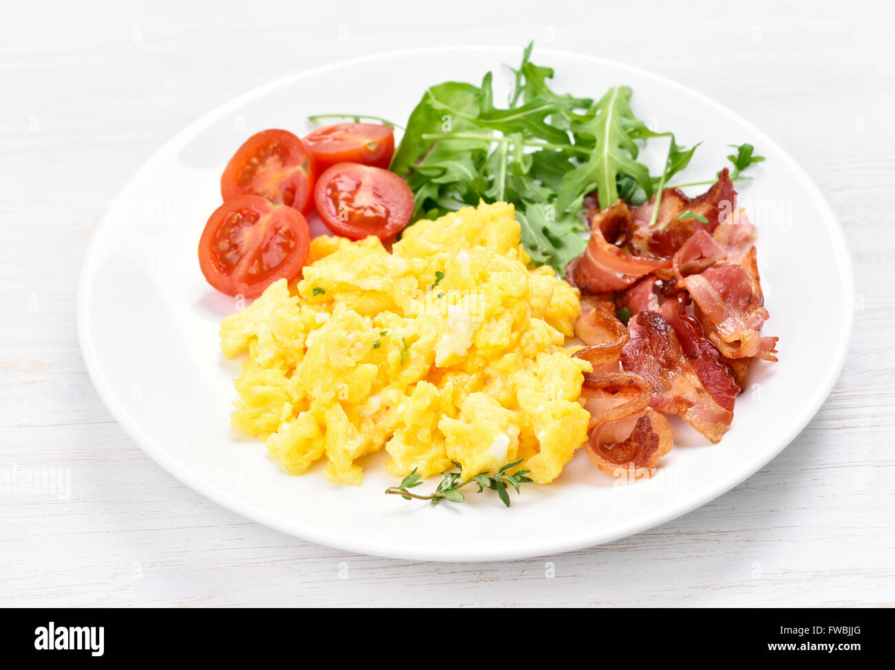 Scrambled eggs, bacon and vegetable salad, close up view - Stock Image