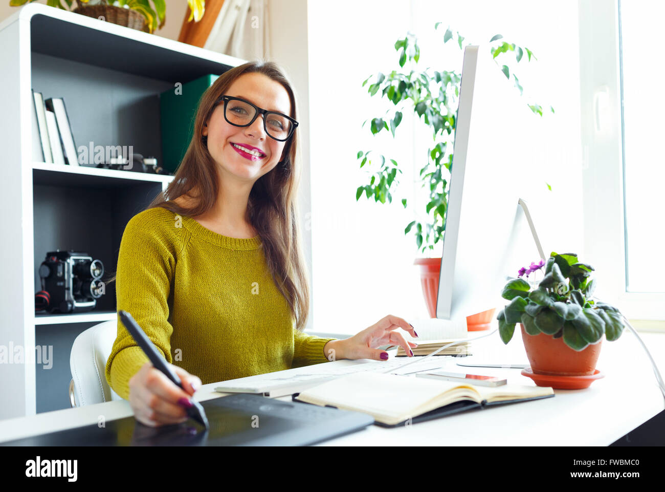 Young artist drawing something on graphic tablet at the home office - Stock Image