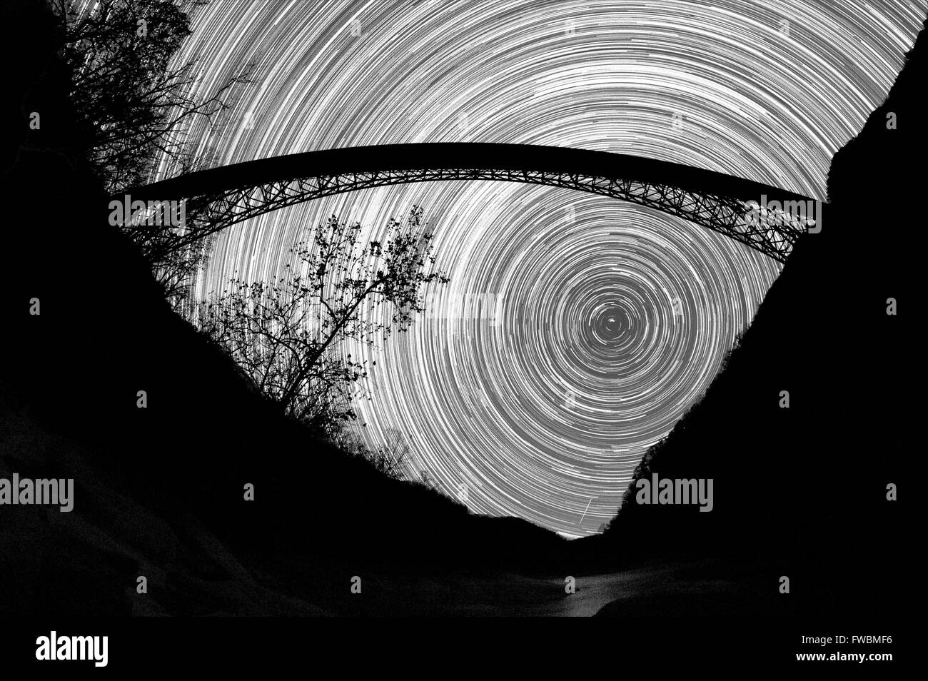 The movement of the stars hang frozen in the sky below a giant arch steel bridge over a gorge in black and white, - Stock Image