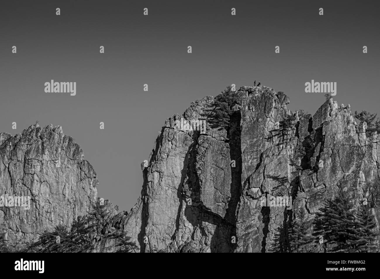 Rock climbers taking a break on top of one of the crags of Seneca Rocks in West Virginia, shown in black and white - Stock Image