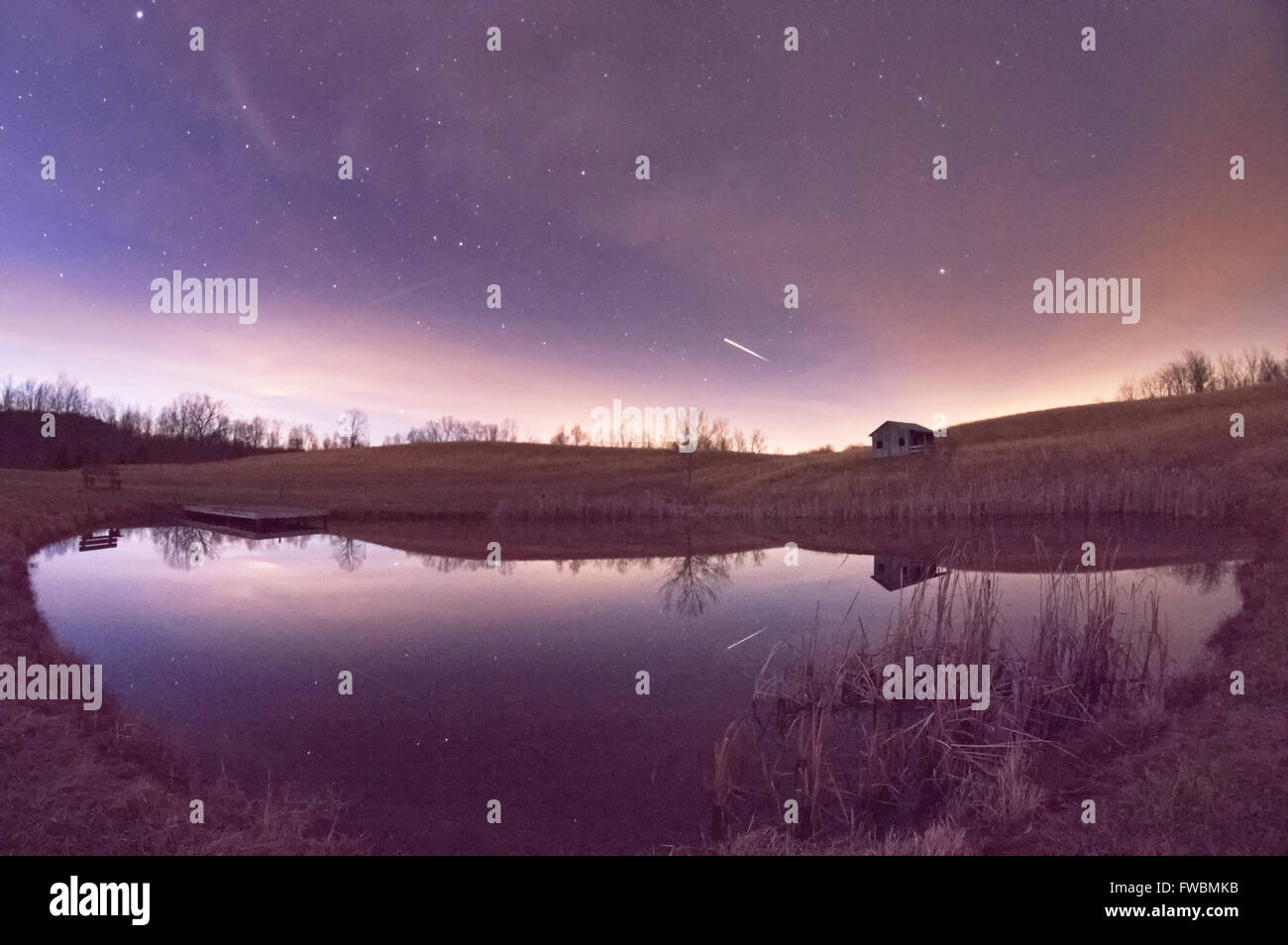 The international space station streaks across the night sky just after twilight reflected off a pond. - Stock Image