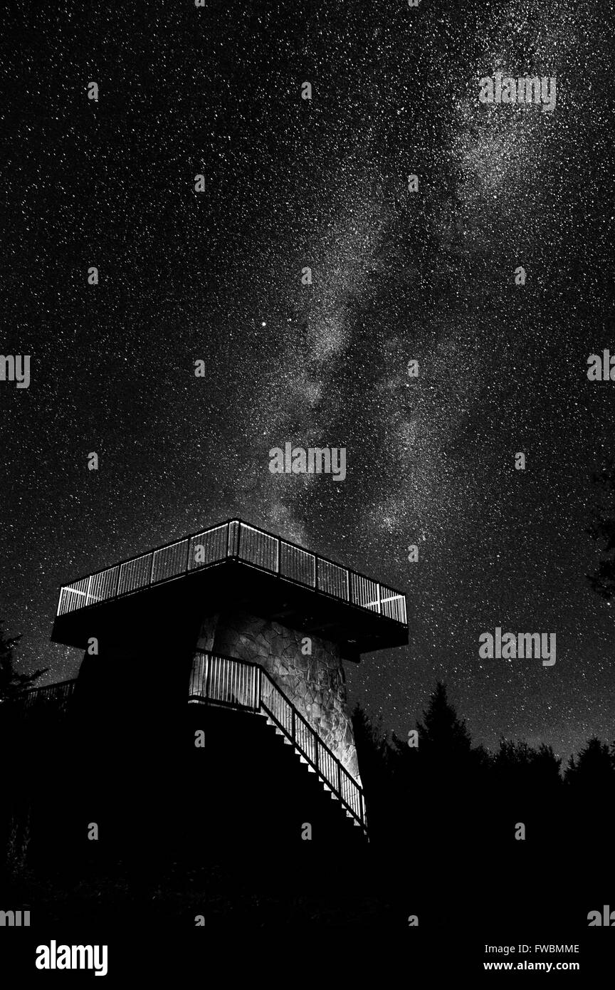 The core of the milky way hangs starkly above the light painted stone structure of an observation tower in black - Stock Image