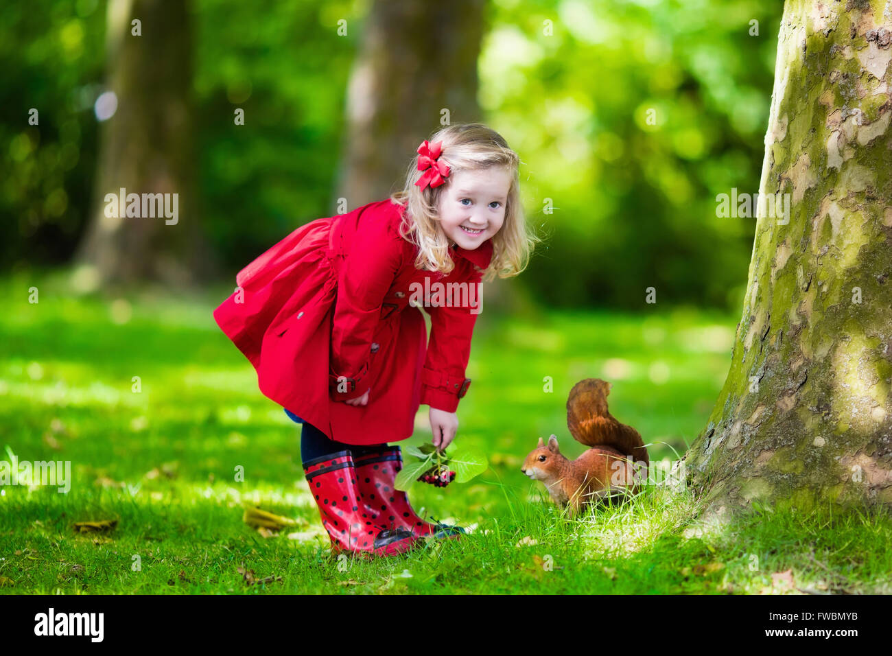 72f50c1fc1b2c Girl feeding squirrel in autumn park. Little girl in red trench coat and  rain boots watching wild animal in fall forest