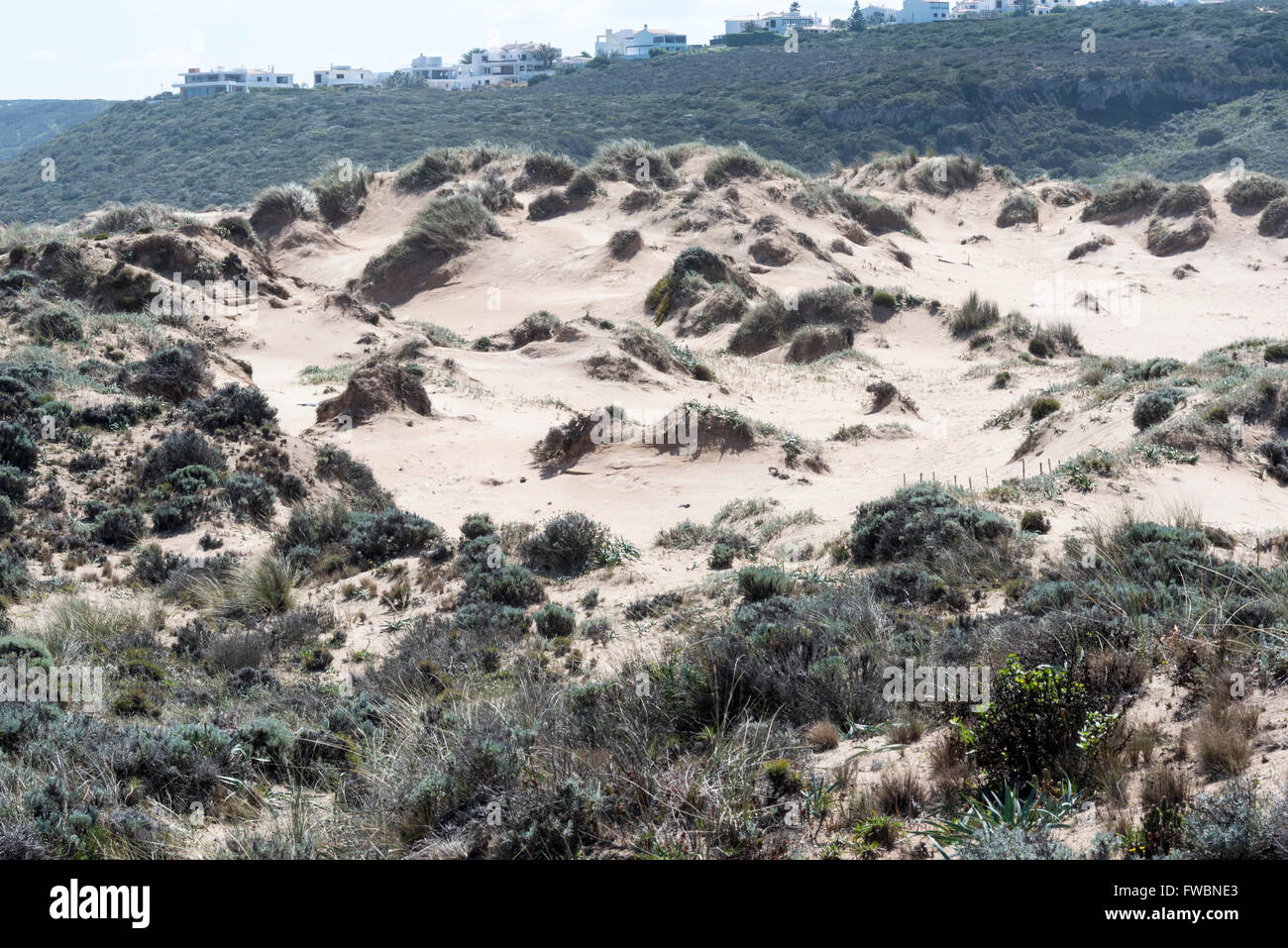 The sand dunes at the mouth of the River Aljezeur with a housing development on the horizon - Stock Image