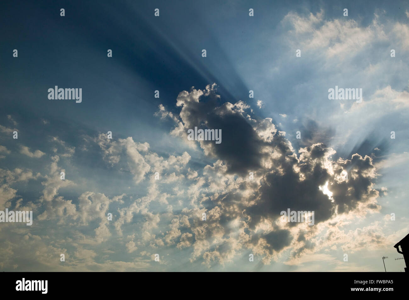Large clouds block out the sun sending huge rays of light spilling out from around the edges. - Stock Image