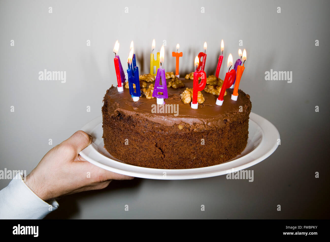 A Large Birthday Cake Is Offered Up For The Blowing Out Of Candles Whihc Edge In Letters Spelling Happy