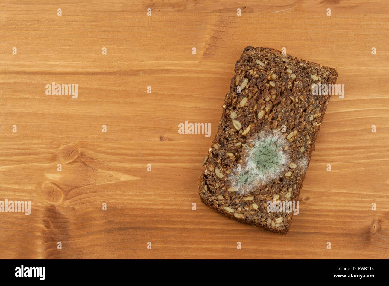 Moldy bread in wooden table. Unhealthy food. Spoiled food. - Stock Image
