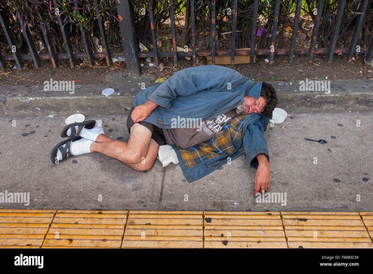 A homeless man sleeping along Avenida 2 in San José, San José Province, Costa Rica. - Stock Image