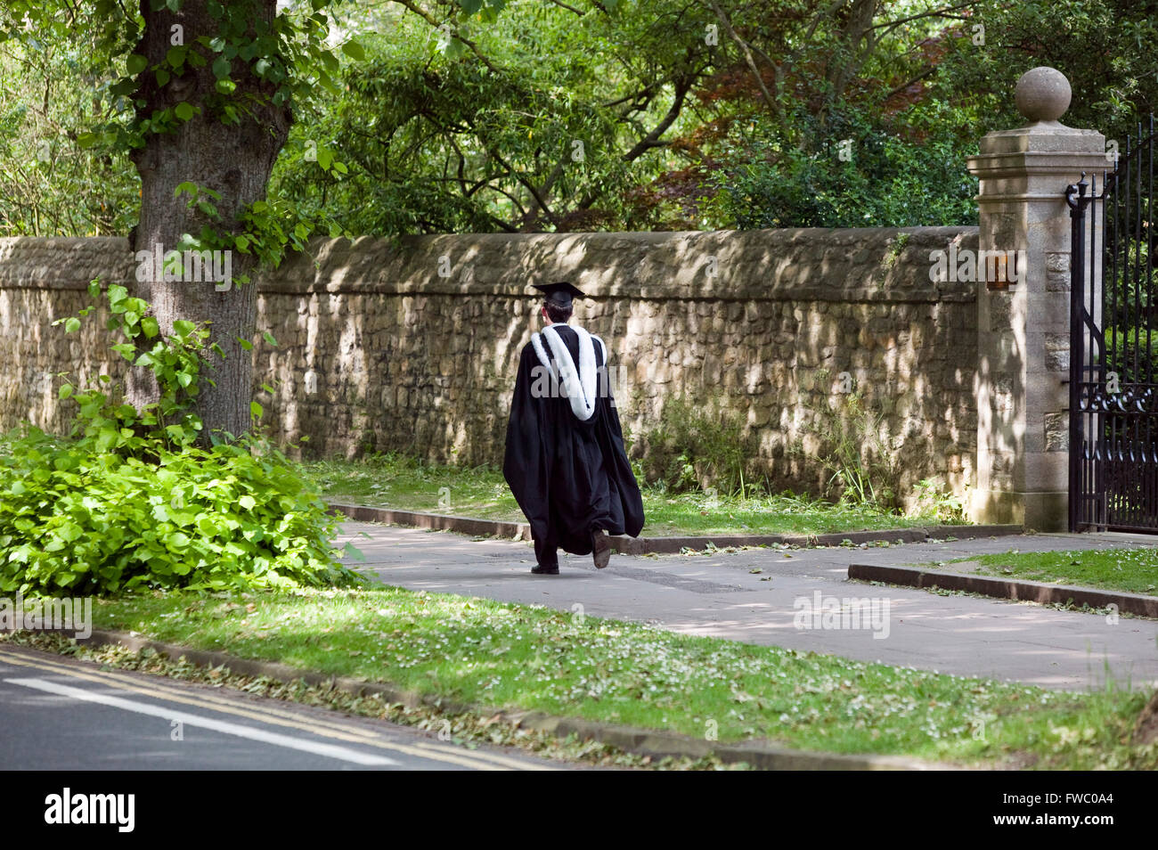 Oxfrod student walking through the streets in gown and mortar board. - Stock Image