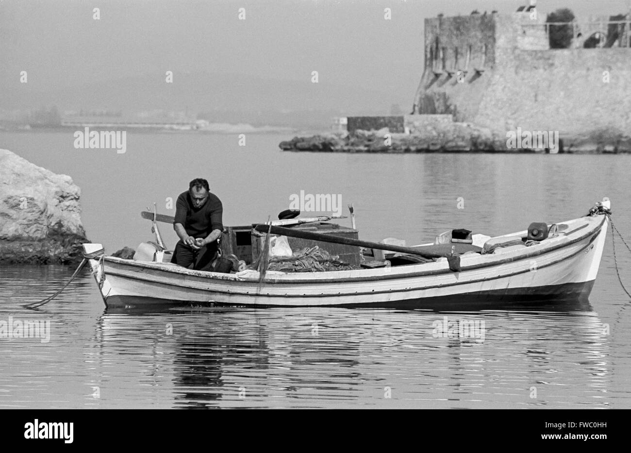 A fisherman in the harbour at Nafplion, in Peloponnisos, Greece. Stock Photo