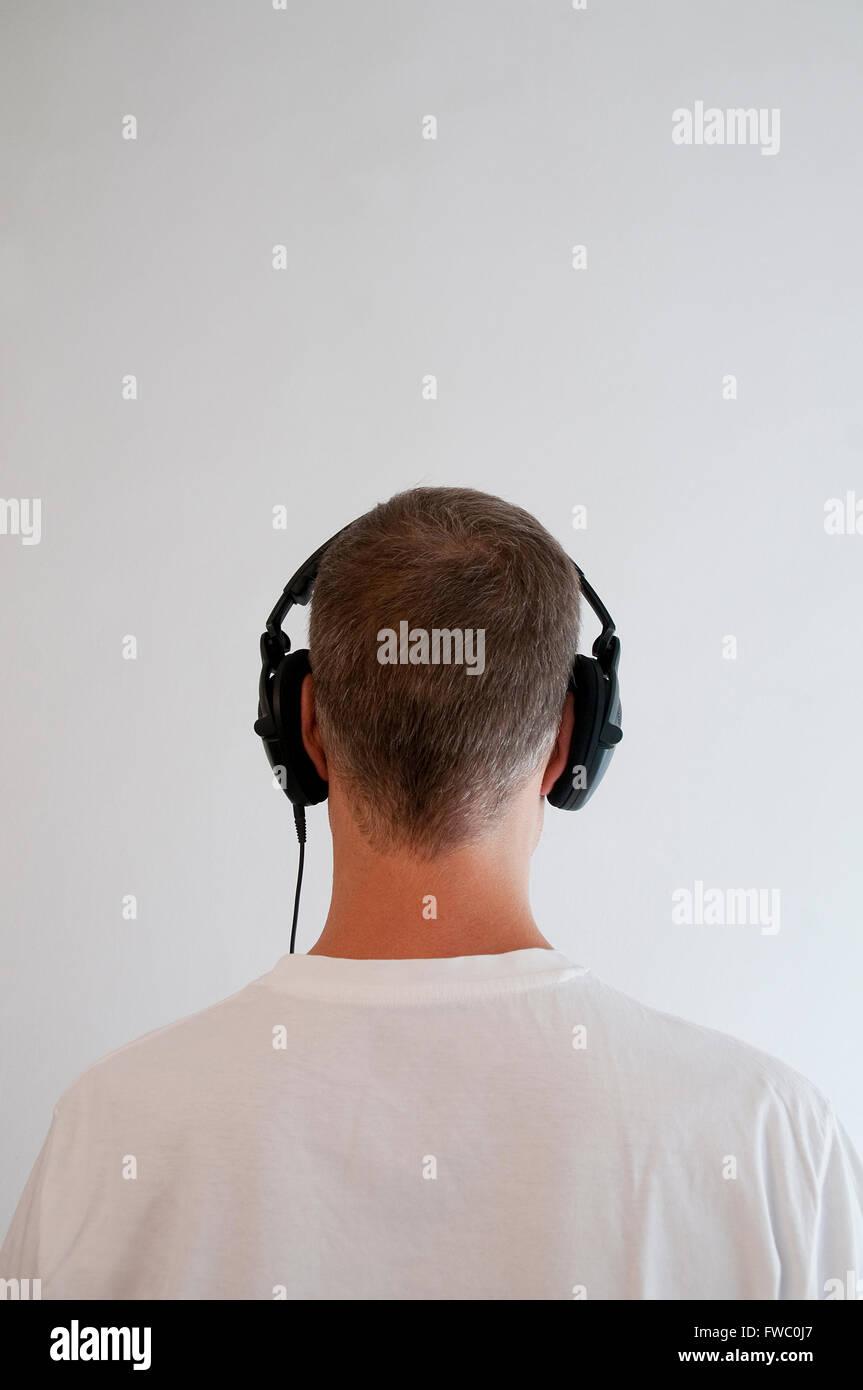 Man listening music using earphones. - Stock Image