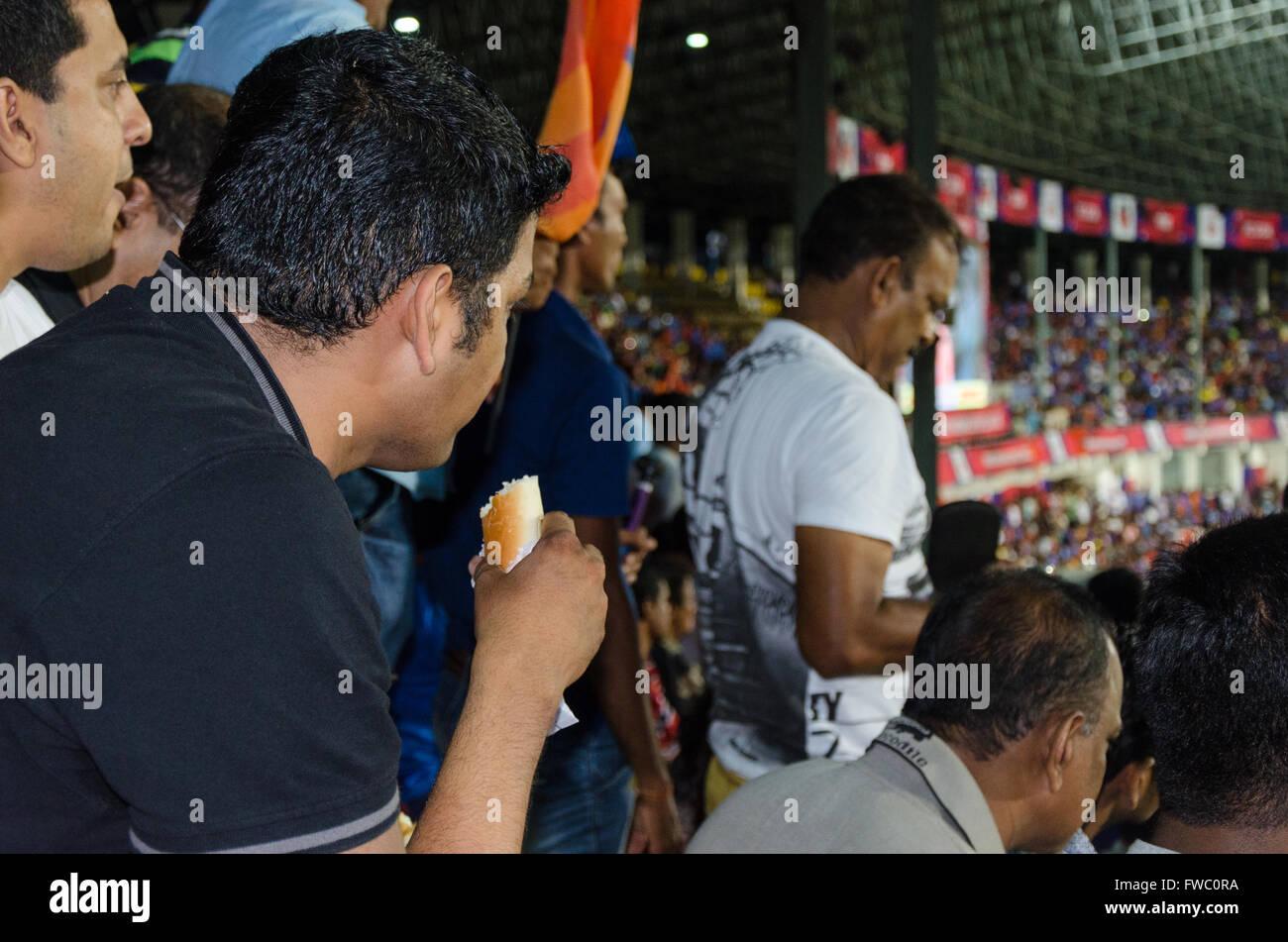 A spectator eats sandwich during halftime of FC Goa vs Atlético de Kolkata ISL match on October 7, 2015 in - Stock Image