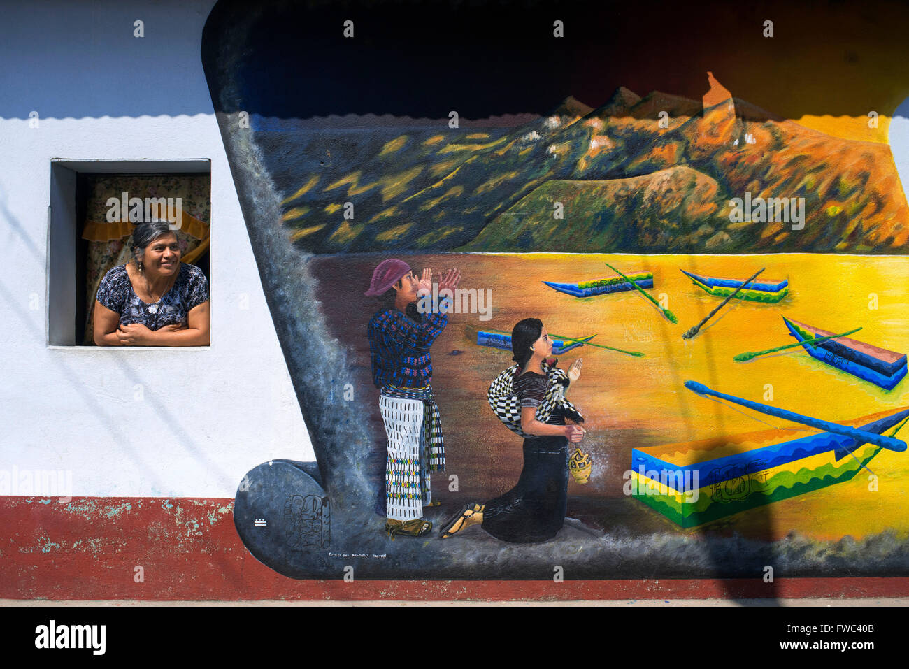 Local woman in a windows next to of a wall panting in San Juan La Laguna, Sololá, Guatemala. Traditional mayan - Stock Image
