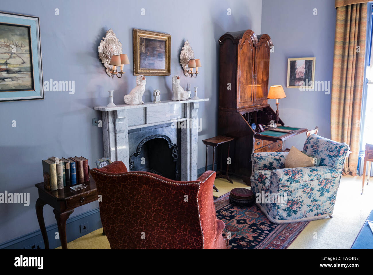 Chairs arranged around a fireplace in the living room of an old-fashioned house - Stock Image