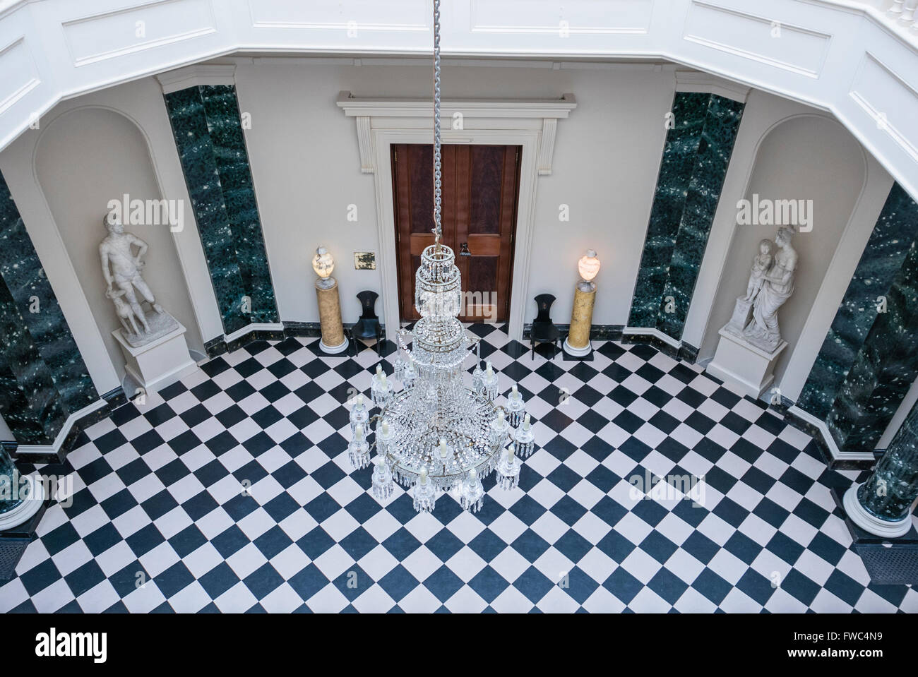 Crystal chandelier hanging over a black and white chequerboard tiled floor in a large entrance hall of a stately Stock Photo