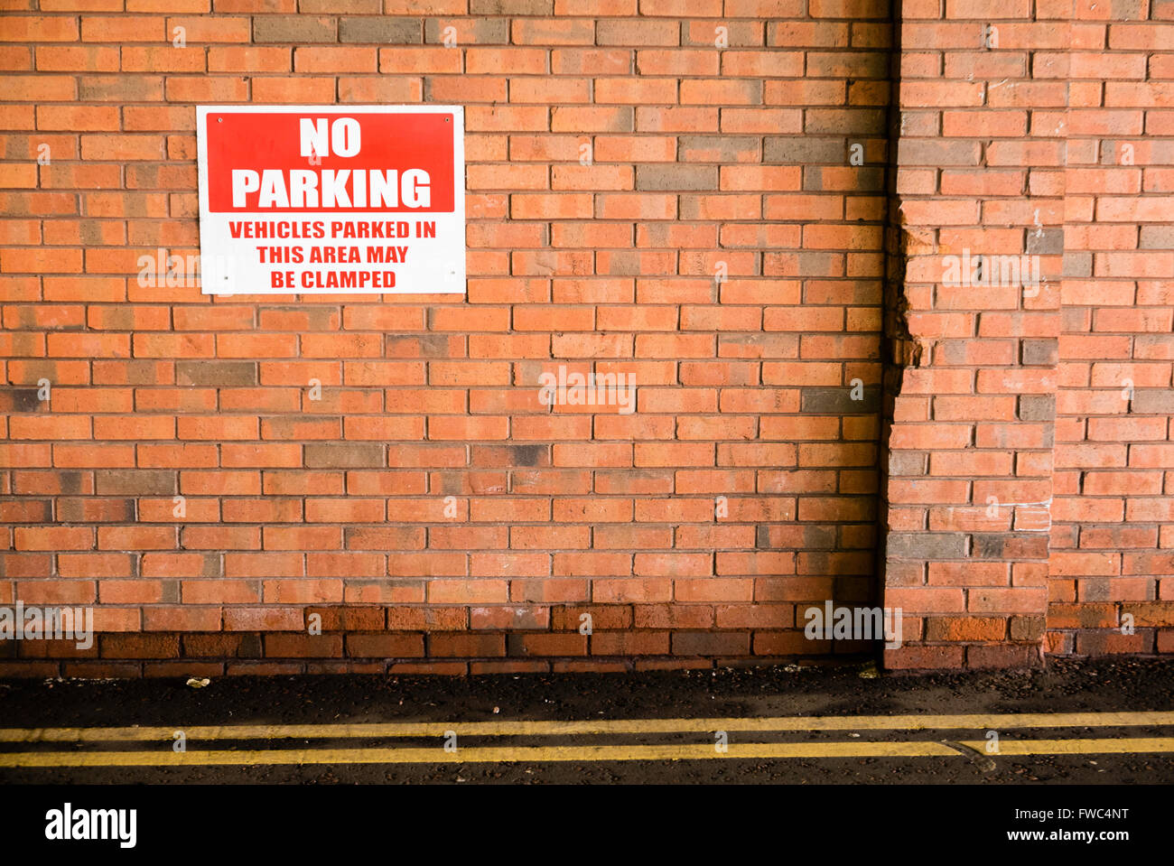 Sign on a brick wall warning that parking is prohibited, and that vehicles parked there may be clamped. - Stock Image