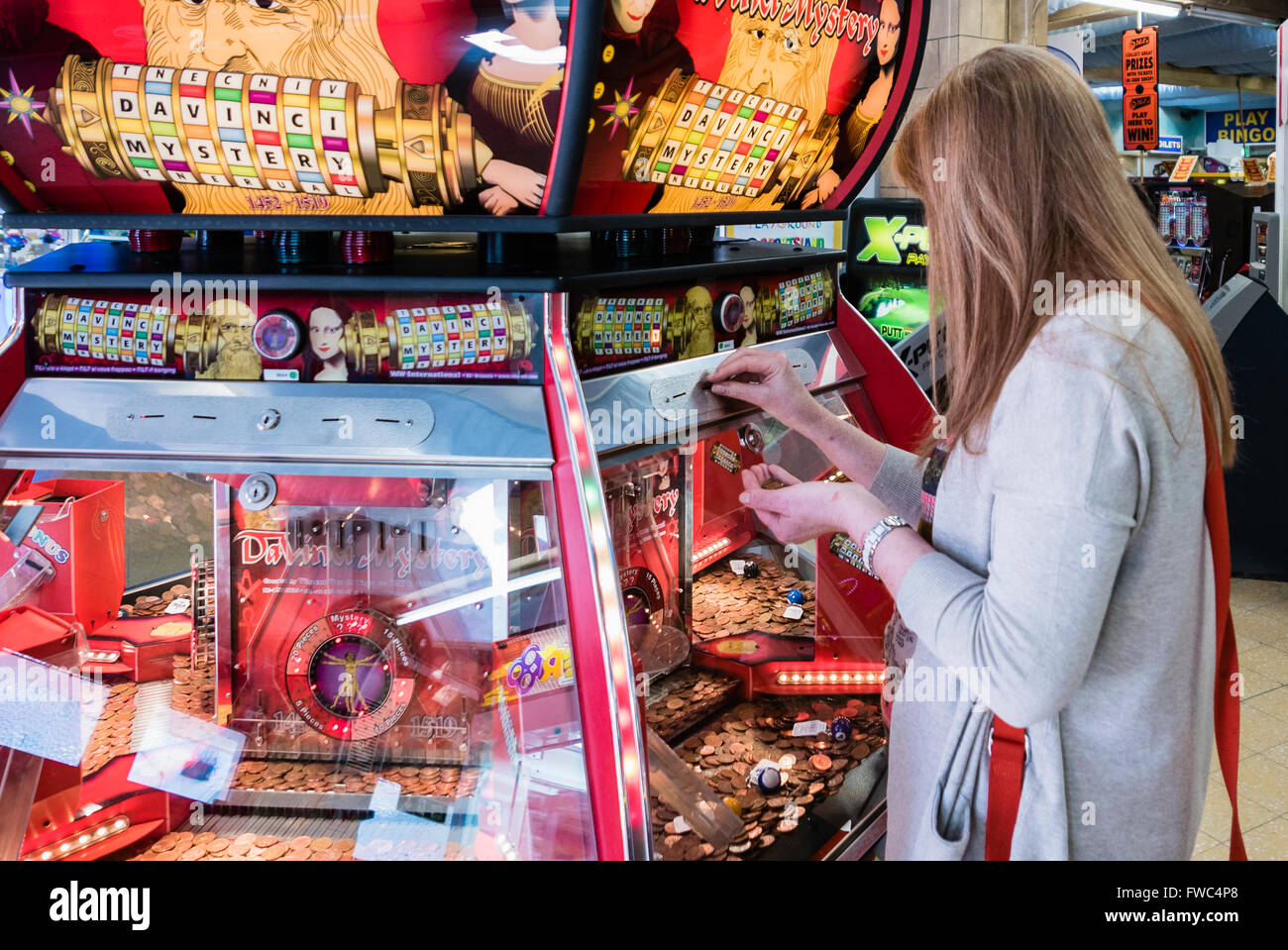 A woman plays a 2p tuppeny nudger machine in a funfair at a British seaside resort. Stock Photo