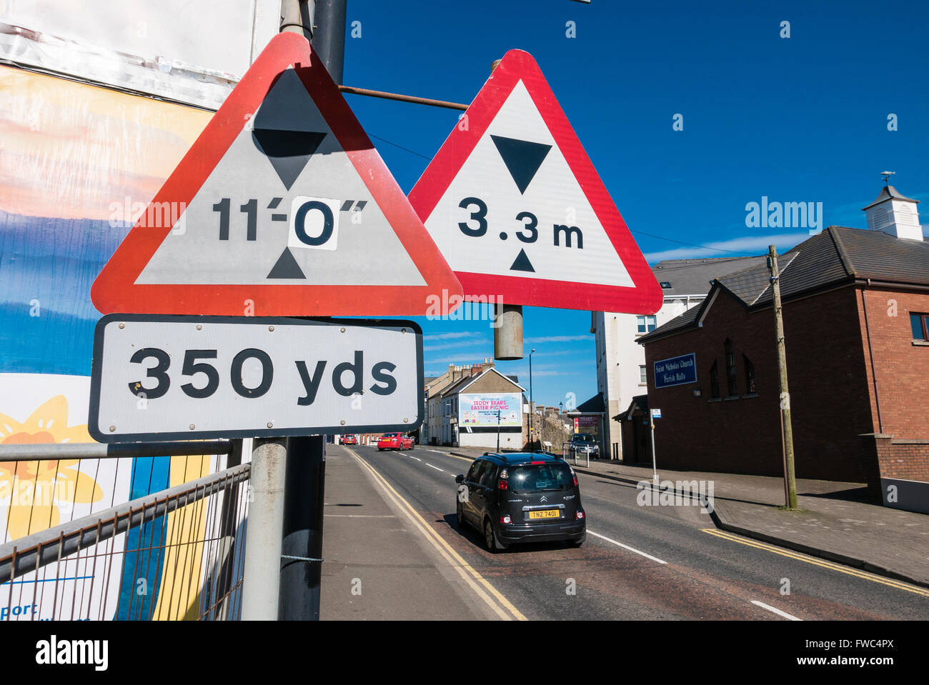 Road sign showing a changed height for an upcoming road bridge, with a new metric sign. - Stock Image
