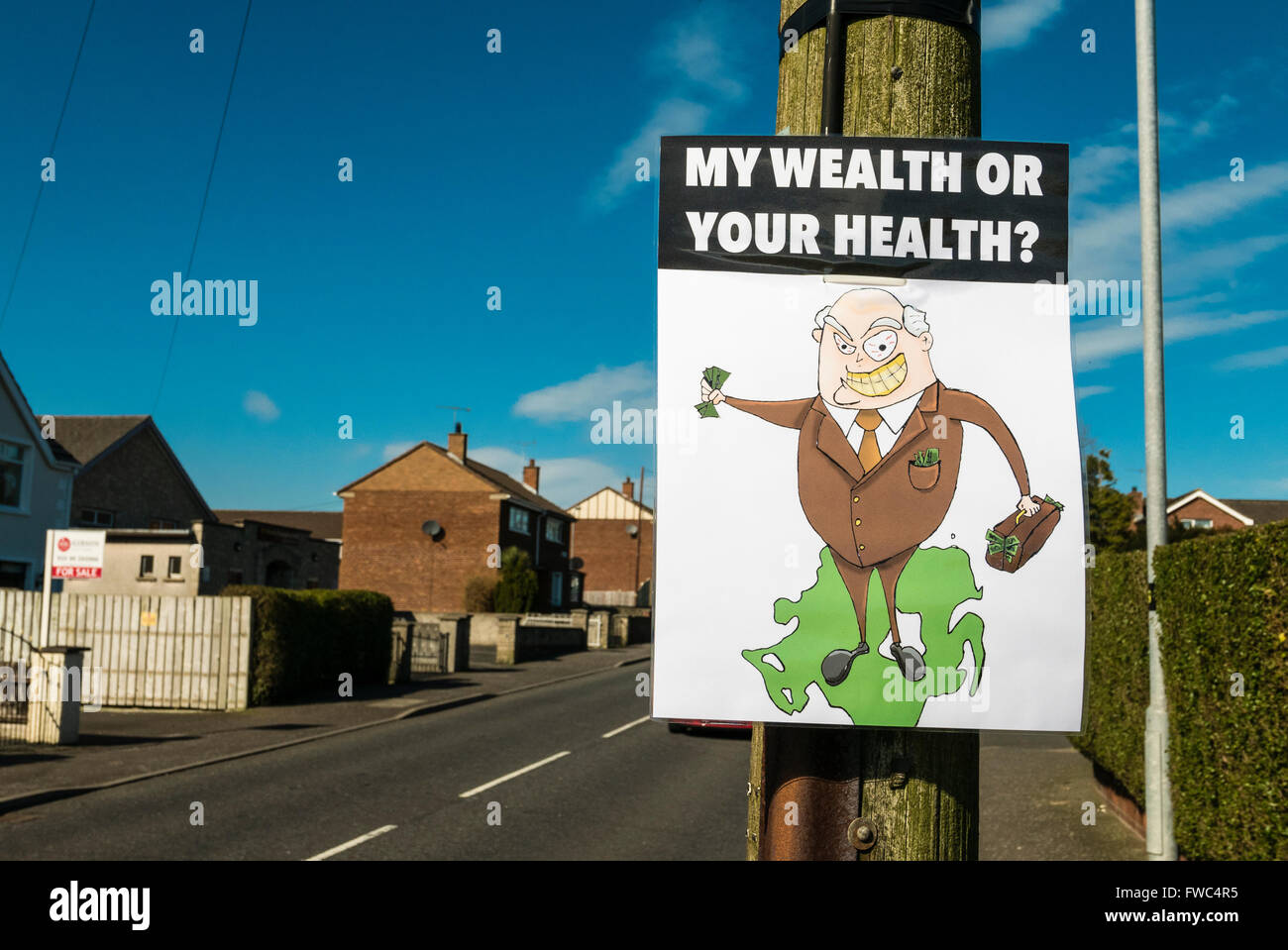 Protest banner attached to a lamppost with the slogan 'My wealth or your health?' - Stock Image