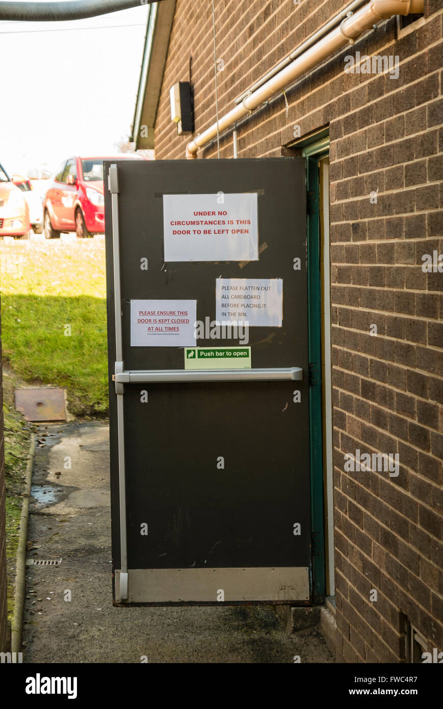 Emergency fire exit door left open on a building, despite signs warning that it should not be left open. Stock Photo