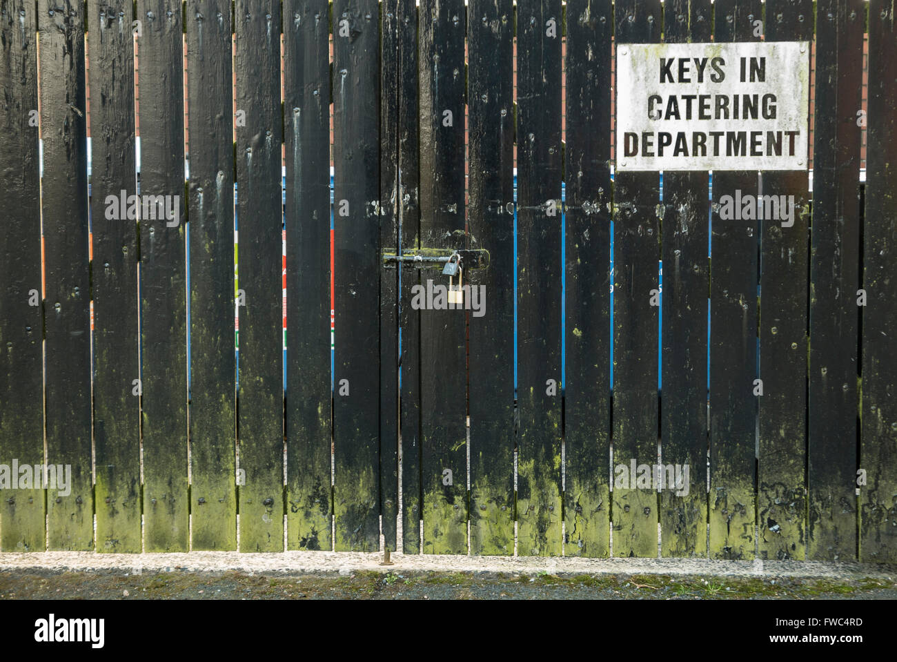 Sign on a locked wooden gate advising people that the keys are available from the catering department. - Stock Image