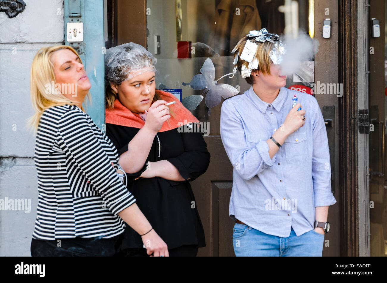 Three women stand at the doorway of a hairdressers shop, smoking and watching something happening. Stock Photo