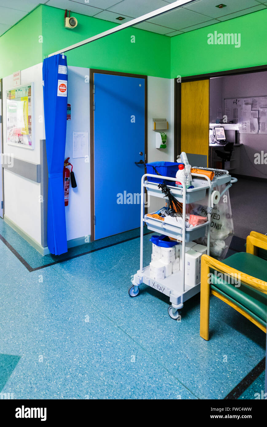 Cleaner's trolley outside a clinical investigation room of a hospital. - Stock Image