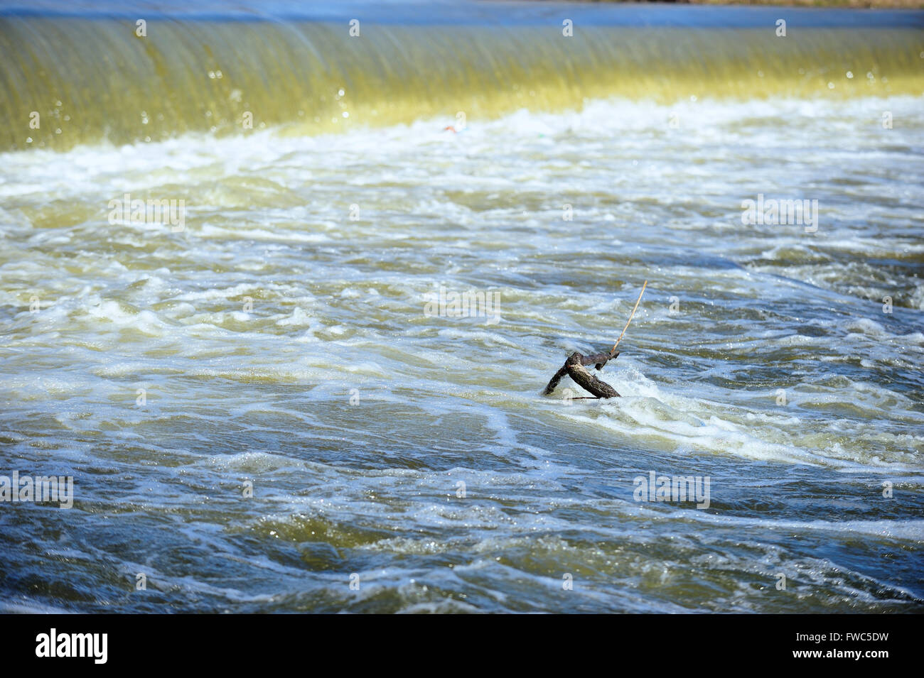 Rushing water pours over a Fox River dam in a swirl of activity. South Elgin, Illinois, USA. - Stock Image