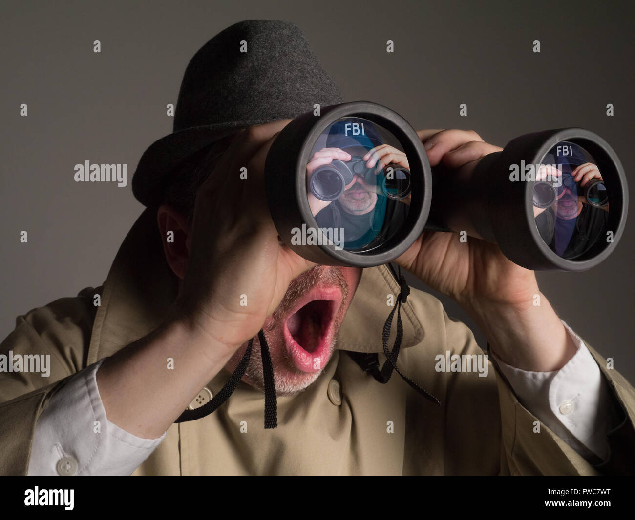 Photograph of NSA agent in trench coat and hat looking through binoculars. He is shocked to see an FBI agent watching - Stock Image