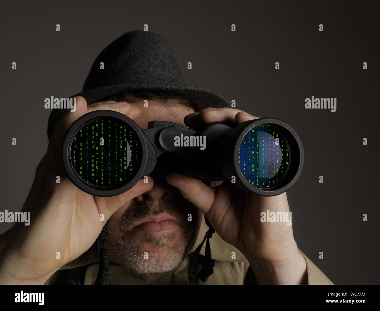 Photograph of a man in trench coat and hat looking through binoculars at computer code. - Stock Image