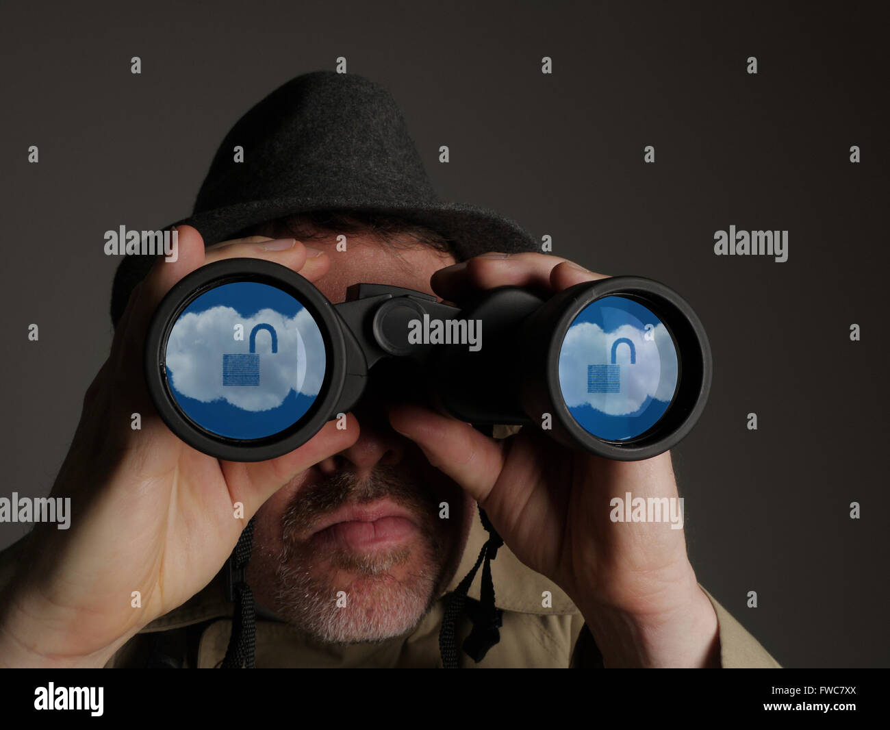 Photograph of a man in trench coat and hat looking through binoculars with reflected cloud symbols in the lenses. - Stock Image