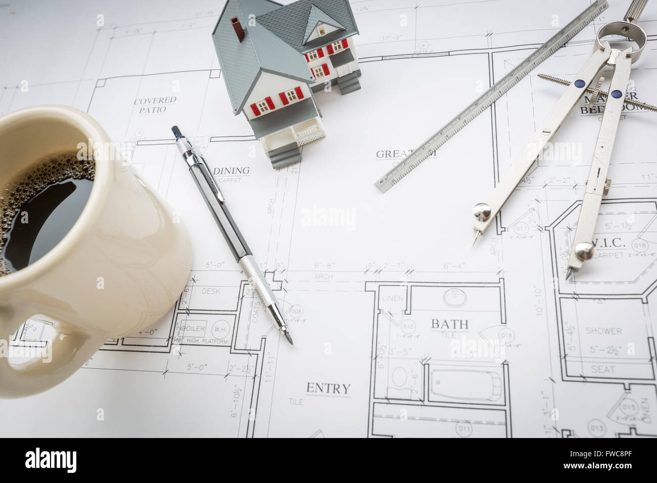 Model Home, Cup of Coffee, Pencil, Ruler and Compass Resting