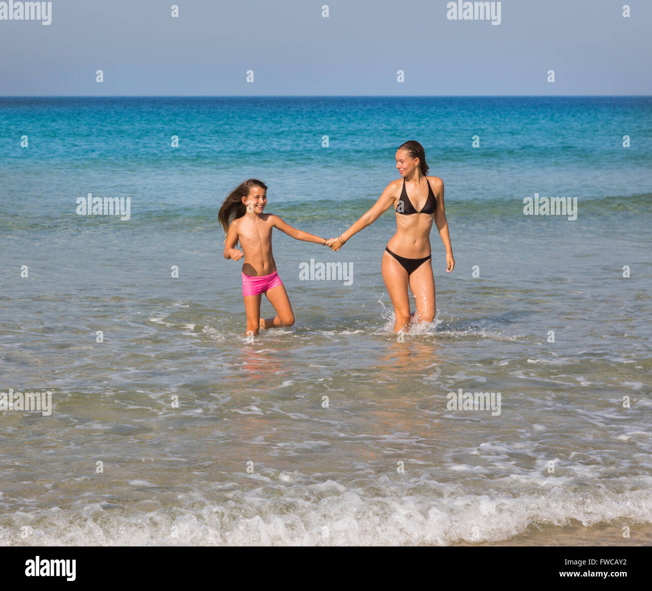 Tarifa, Costa de la Luz, Cadiz Province, Andalusia, southern Spain.  Seven year old and fifteen year old girls playing - Stock Image