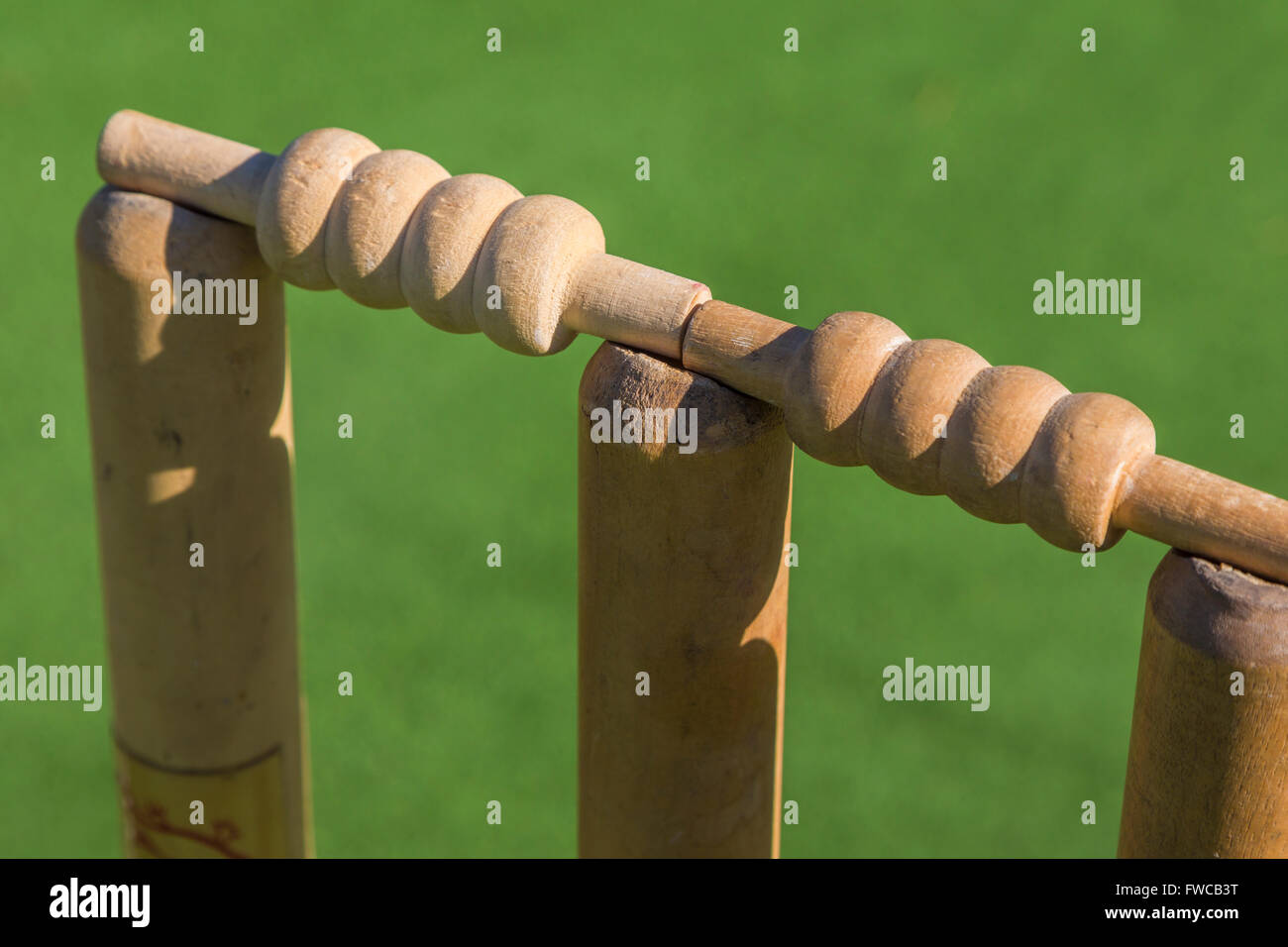 Well used cricket stumps and bails set up on pitch.  Grassy green background. - Stock Image