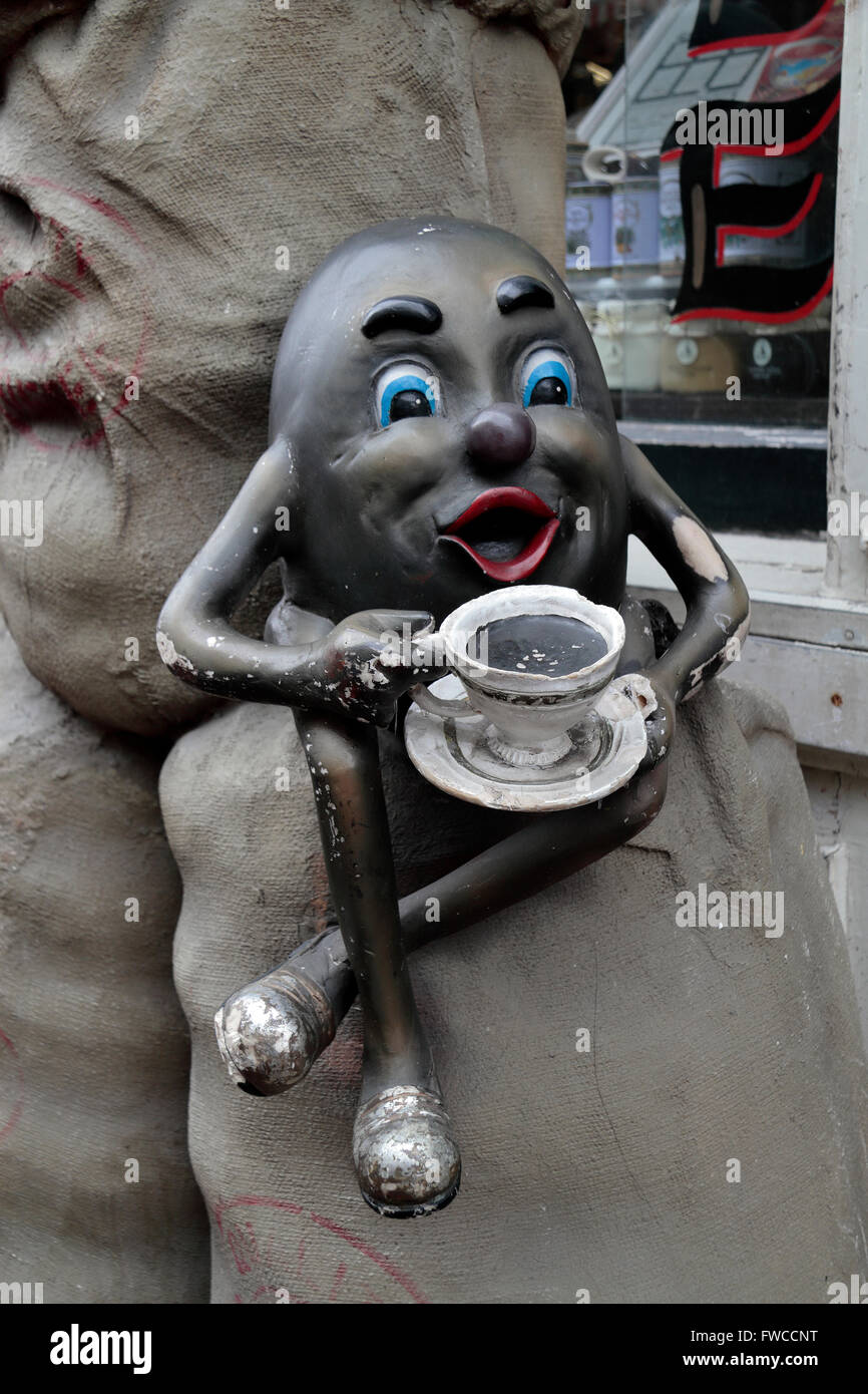 Amusing coffee bean figure with legs drinking coffee outside the 'Thee Koffie' coffee shop in Amsterdam, - Stock Image