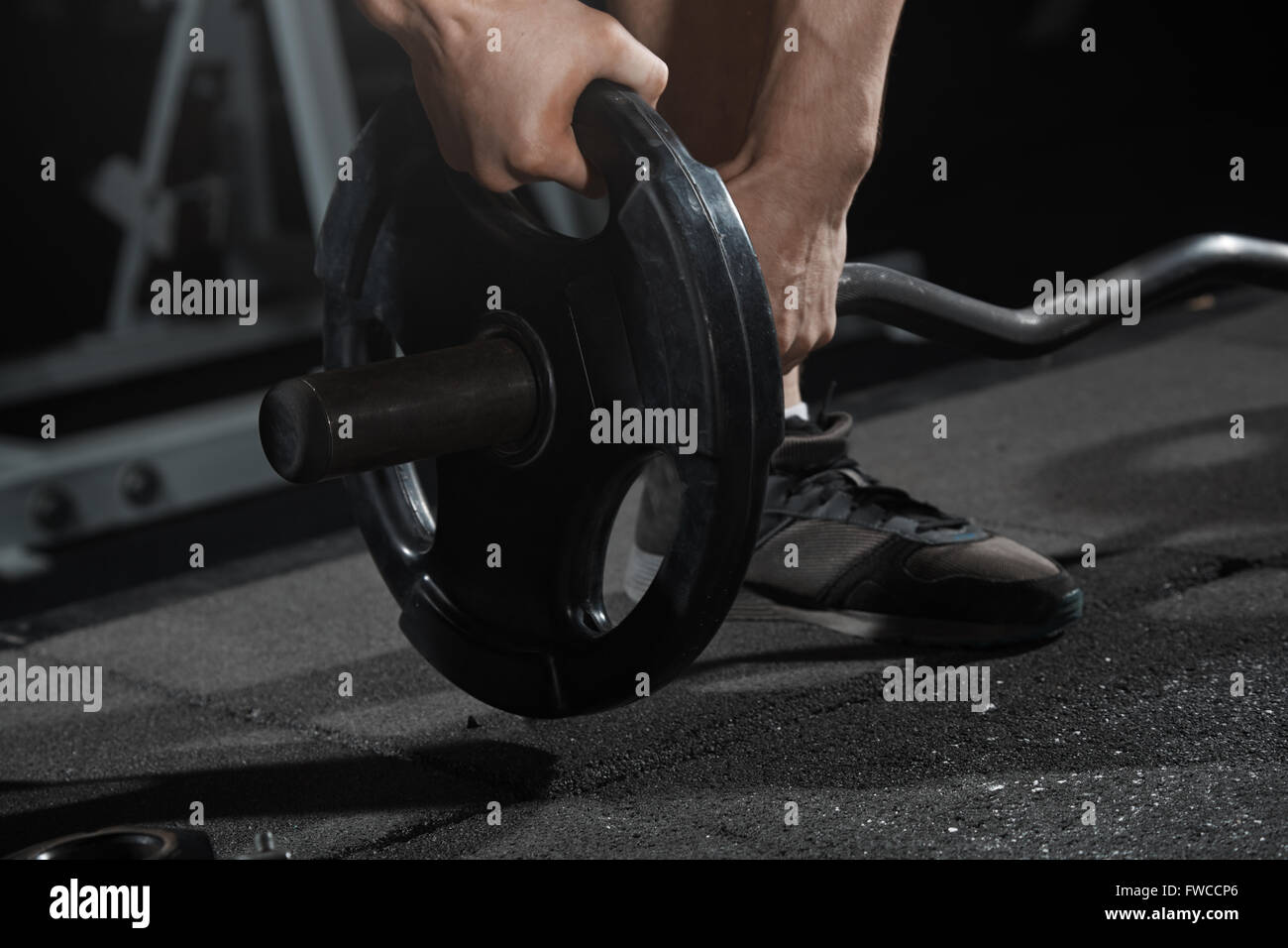 Man preparing barbell at fitness club - Stock Image