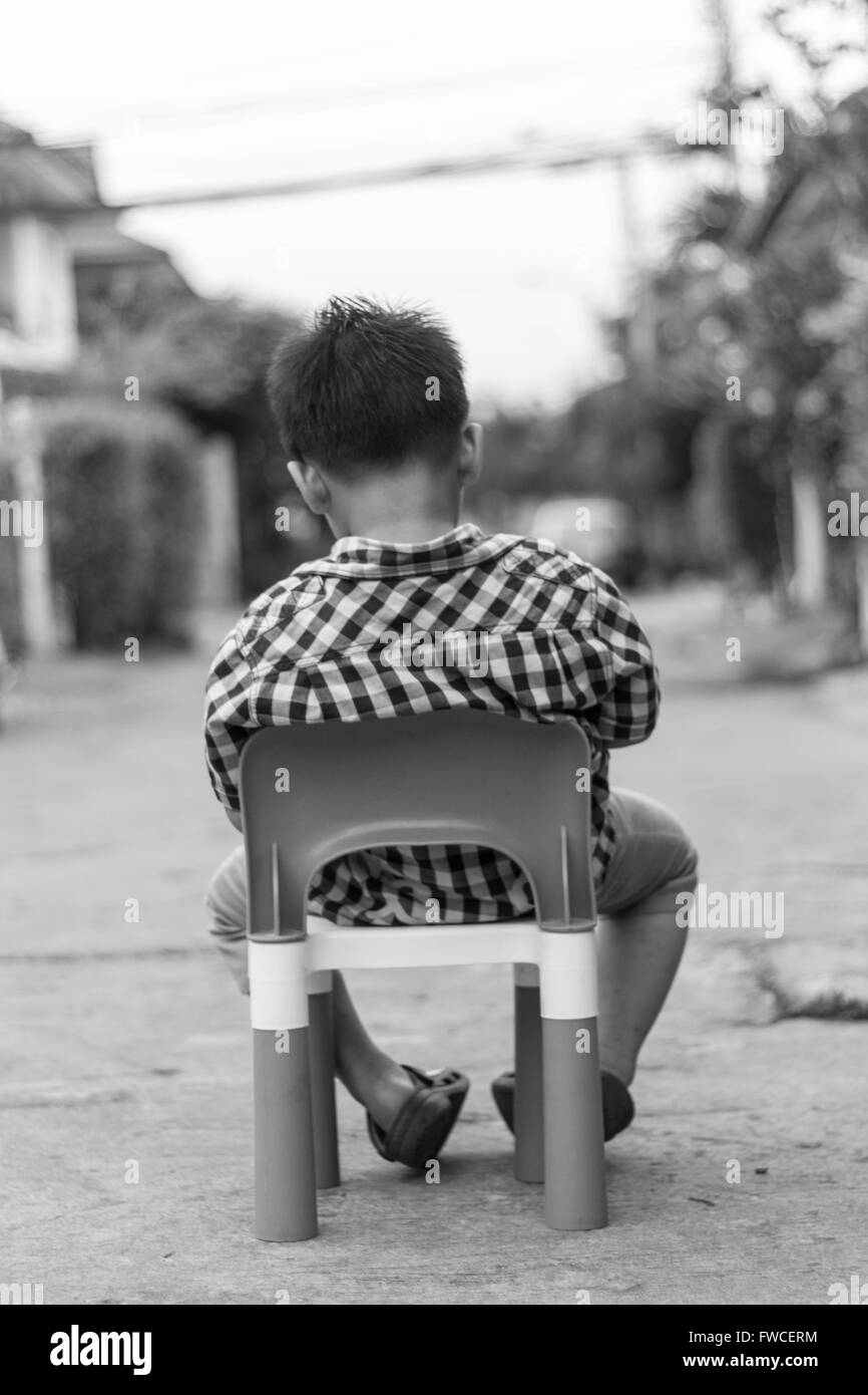 Alone boy sit on the plastic chair on the concrete road stock image