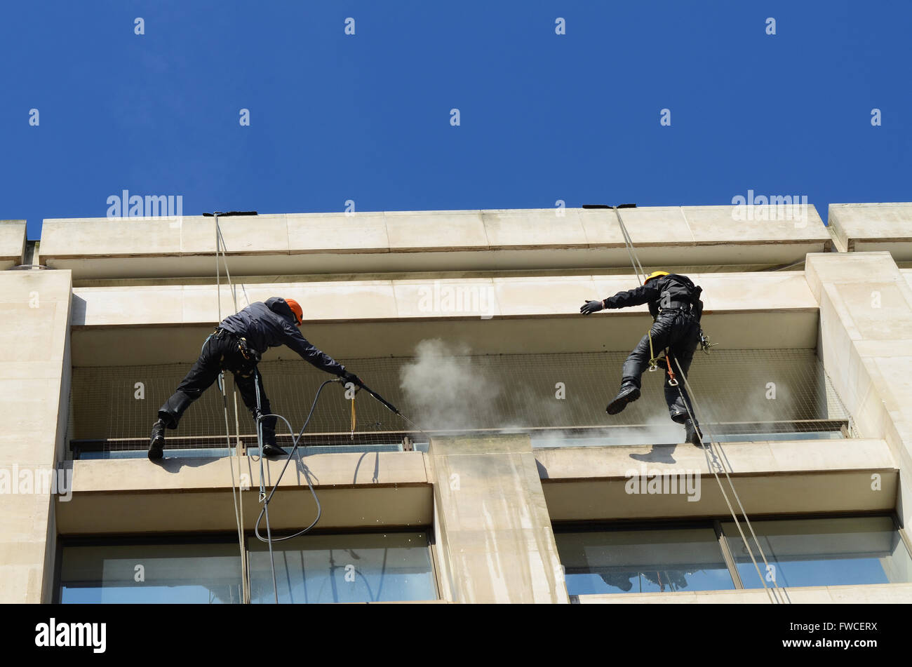 Rope access, abseiling, provides window cleaning access for hard to reach glass and stonework. Male working at height Stock Photo