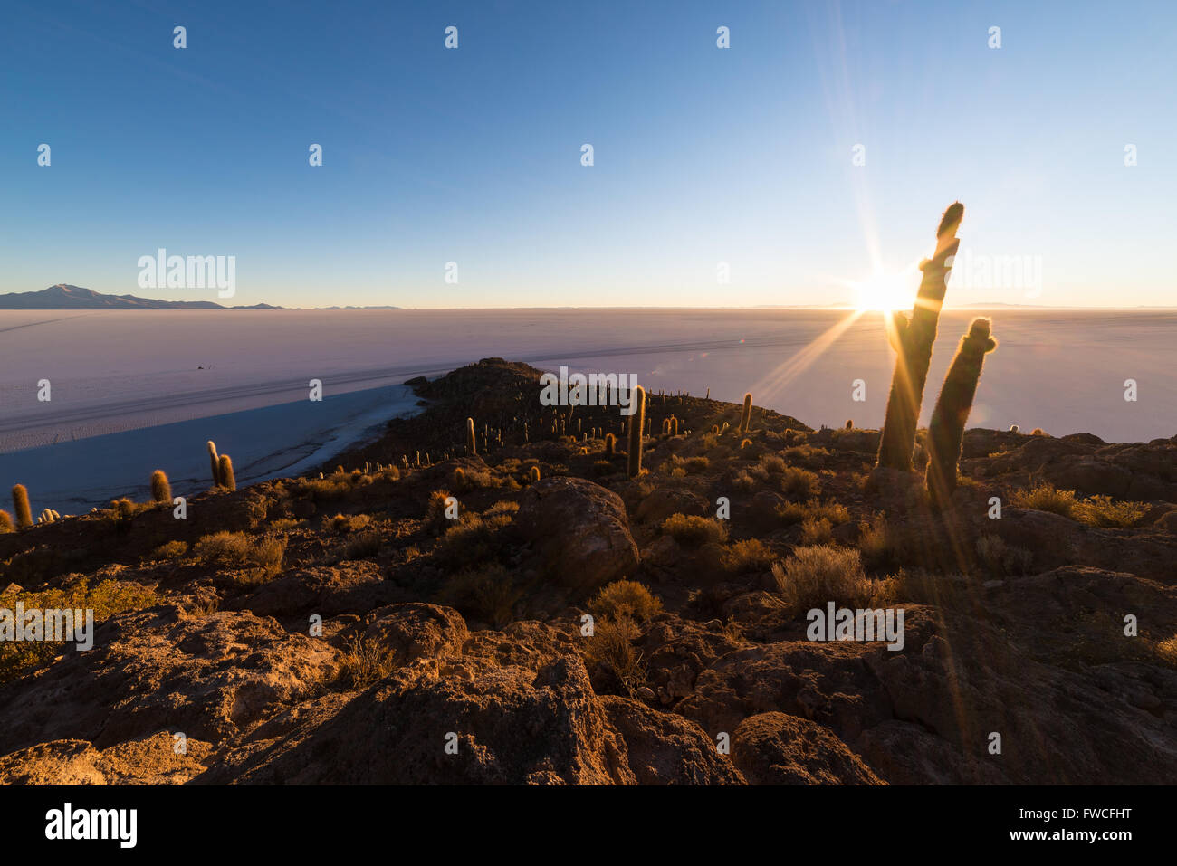 The rising sun at the horizon over the majestic Uyuni Salt Flat, among the most important travel destination in - Stock Image