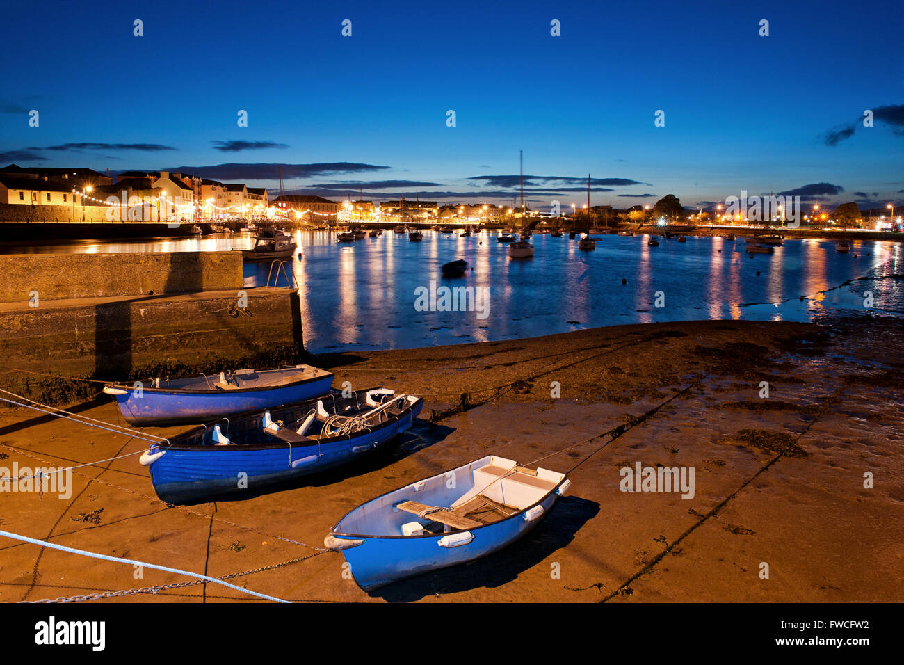 Boats moored at Dungarvan Harbour with the lights and blue evening sky over Dungarvan Town, Dungarvan, Waterford, - Stock Image