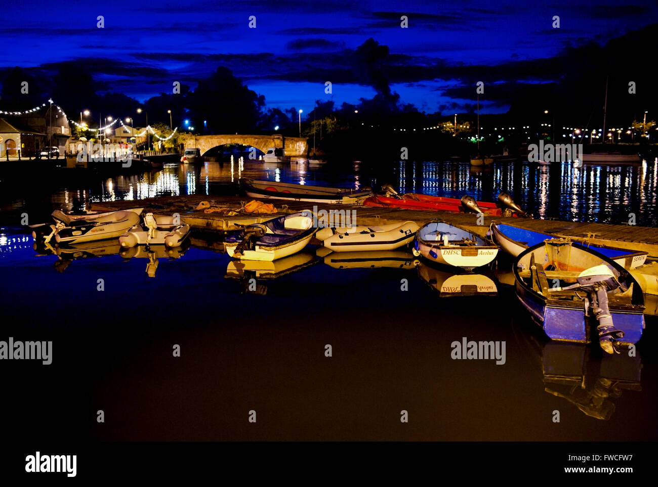 Boats moored at Dungarvan Harbour reflected in the calm water with the lights and blue evening sky over Dungarvan - Stock Image