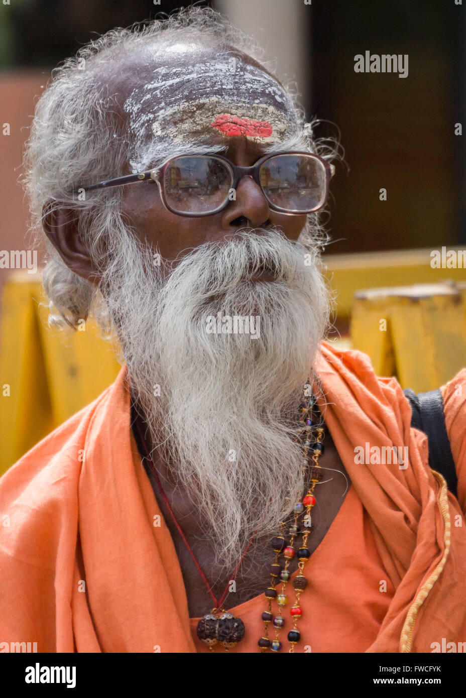 Trichy, India - October 15, 2013: Old, graying sadhu with beard and glasses. Wears orange garb and has his forehead - Stock Image