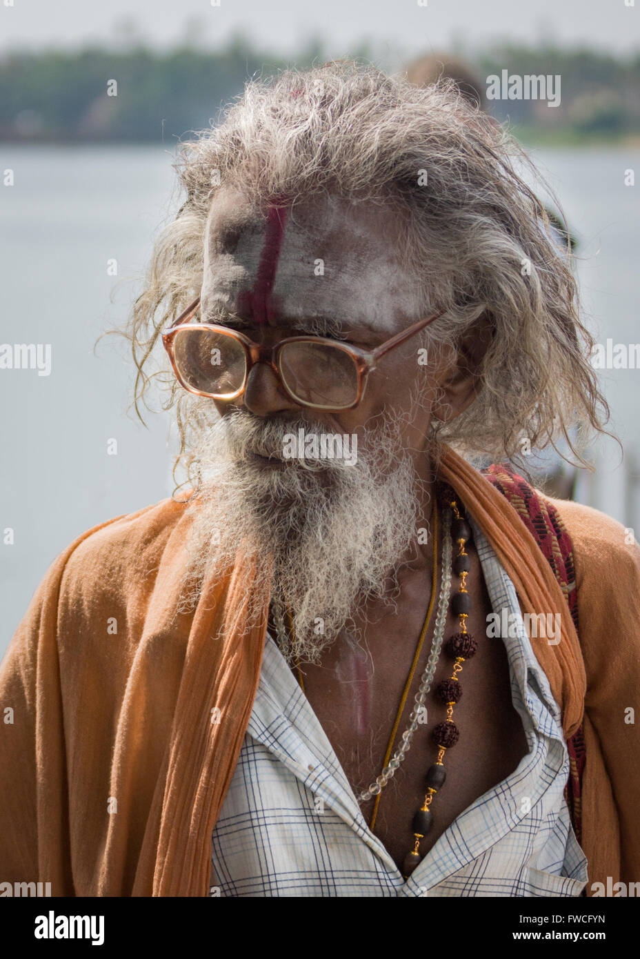 Trichy, India - October 15, 2013: Old, graying sadhu with beard and glasses. Wears orange garb. - Stock Image