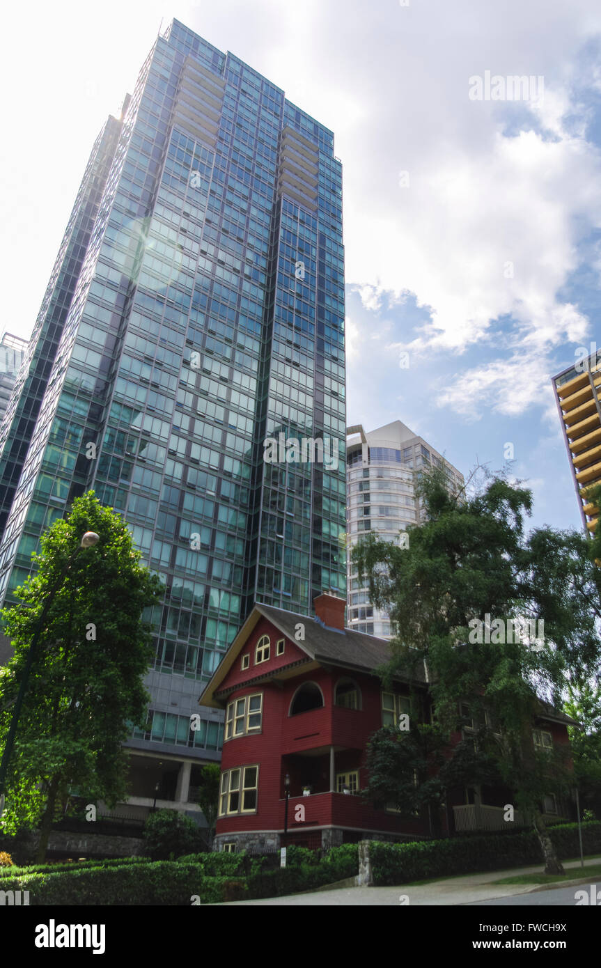 Small old house being overshadowed by a modern high-rise building in Vancouver, British Columbia, Canada. - Stock Image