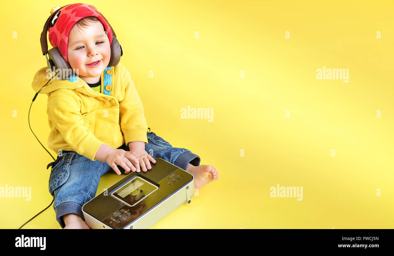 Satisfied cute, little boy listening to music - Stock Image