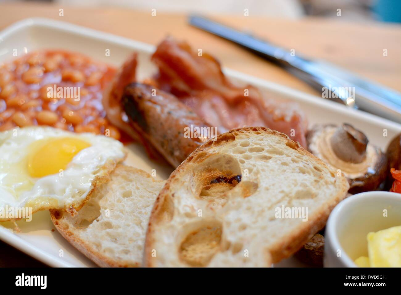 Cooked breakfast with toast, bacon, fried egg, sausage, baked beans, mushroom and butter - filter applied - Stock Image