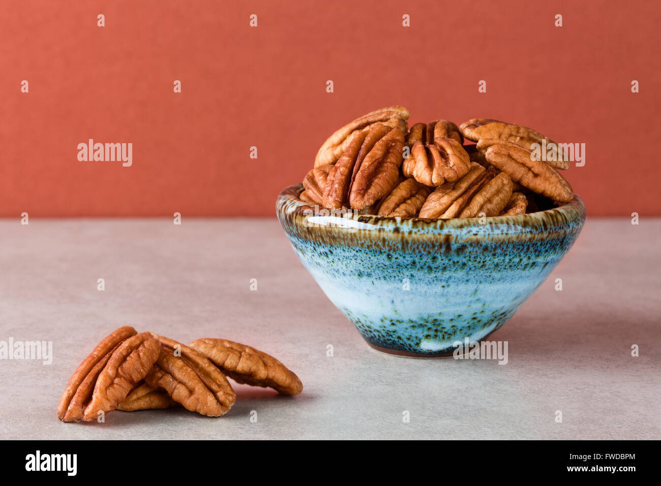 Pecans on marble surface and in ceramic bowl with brown background. Copy space, shallow depth of field - Stock Image