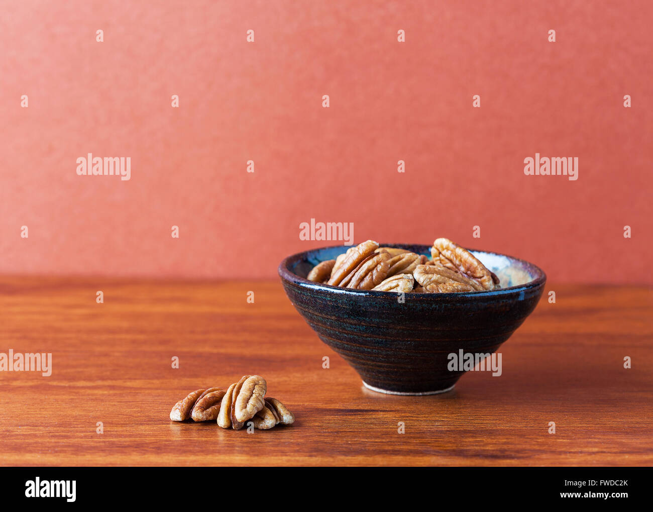 Pecans on wooden table and in ceramic bowl with brown background. Copy space, shallow depth of field - Stock Image