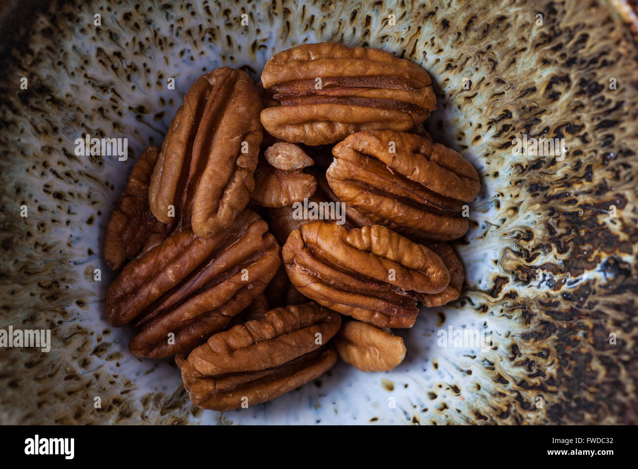 Pecans in handmade ceramic bowl extreme closeup, top view. - Stock Image